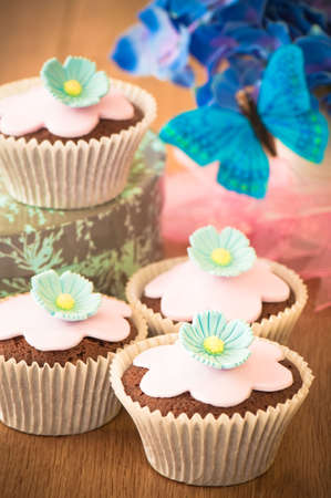 Decorated chocolate cupcakes with pink icing and flower petals photo