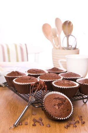sifter: Freshly baked chocolate chip muffins on kitchen table ready to be iced Stock Photo