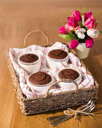 Basket of chocolate cakes with flower arrangement on table photo