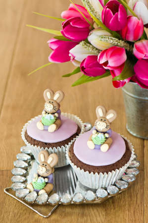 Easter bunny cupcakes sitting on decorative mirror with flower arrangement photo