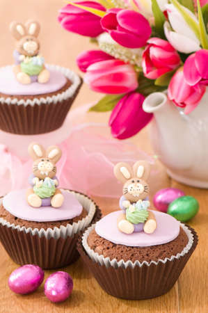 Little Easter bunny cupcakes with foil wrapped eggs and teapot of spring tulips in background photo