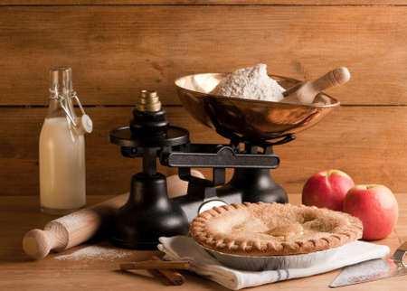 Rustic homemade apple pie with weighing scales and ingredients photo