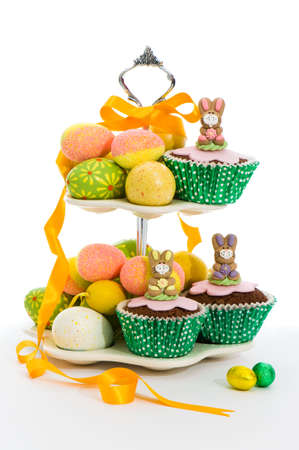 Cute little Easter bunny cakes on stand with Easter eggs and ribbon photo