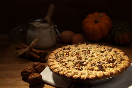 Freshly baked pumpkin pie decorated with pecan, walnuts and pumpkin seeds photo