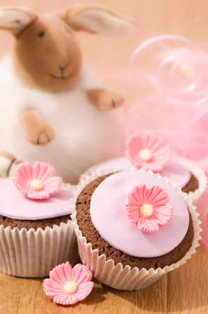 Pretty pink decorated cupcakes for Easter with bunny in background photo