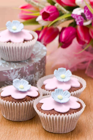 Cupcakes decorated with flowers for springtime with tulips in background photo