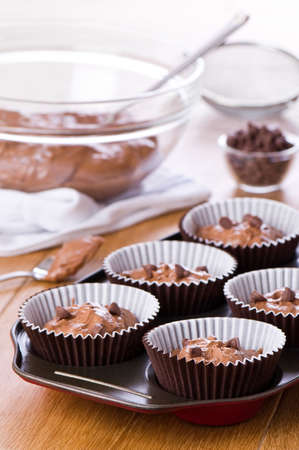 Chocolate chip cake mix in cupcake cases ready for baking photo