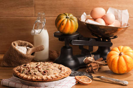 Pumpkin pie with weighing scales and baking ingredients  Stock Photo