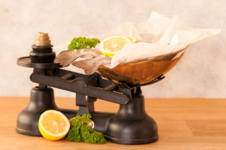 Rainbow trout fish on old fashioned weighing scales with lemon and parsley photo