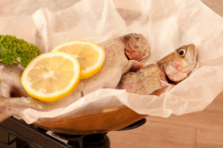 Close up of rainbow trout fish on antique weighing scales with lemon and parsley photo