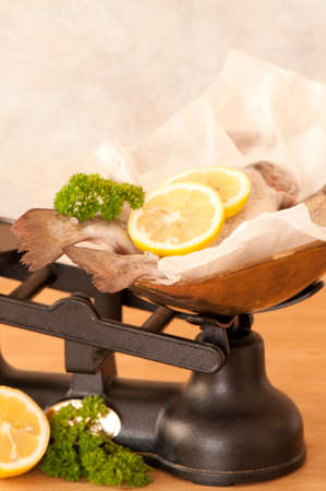 Rainbow trout with lemon and parsley herb on old fashioned weighing scales photo