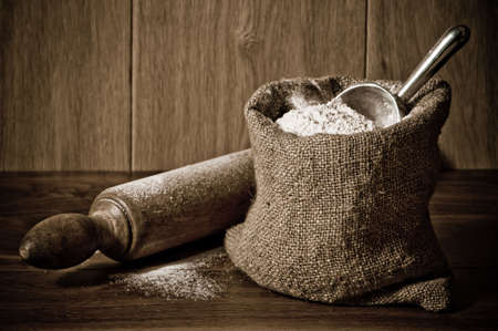 ingredient: Wholemeal wheat flour in burlap sack with antique rolling pin Stock Photo