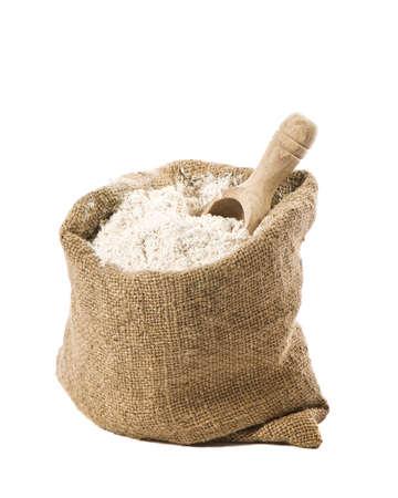 harina: Saco de yute de harina de pan integral con cuchara de madera sobre fondo blanco
