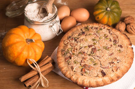 stick of cinnamon: Pumpkin pie decorated with pecan nuts and walnuts Stock Photo