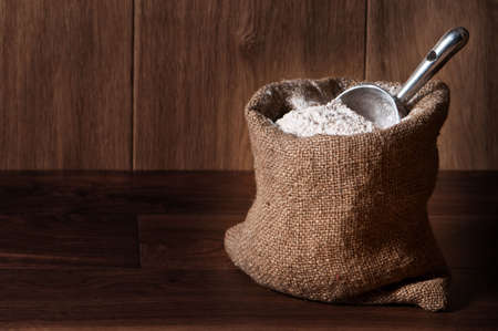 pastry bag: Wholemeal wheat flour in burlap sack with scoop, copy space included