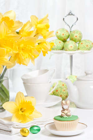 stand teapot: Festive Easter table setting with freshly picked spring daffodils and bunny cupcake