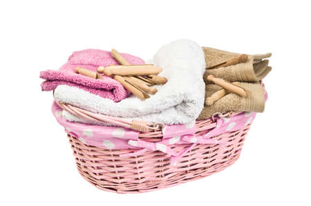 laundered: Basket of freshly laundered towels with old fashioned dolly pegs on white background
