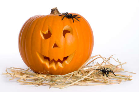 Carved Jack O Lantern on straw with spiders Stock Photo
