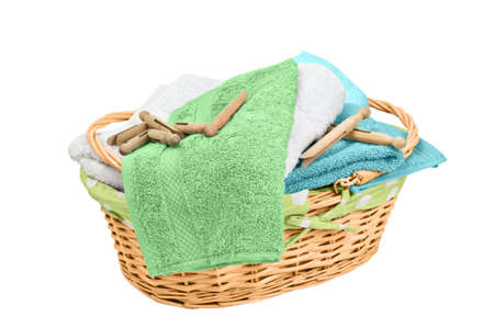 Freshly laundered towels in wicker basket with old fashioned dolly pegs on white background