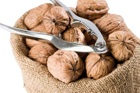 Close up of walnut sack with nutcrackers on white background Stock Photo - 6900235