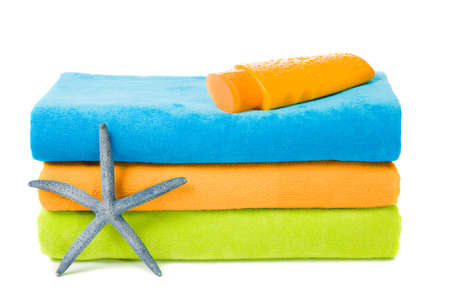 Colorful beach towels with suntan lotion and starfish on white background Фото со стока