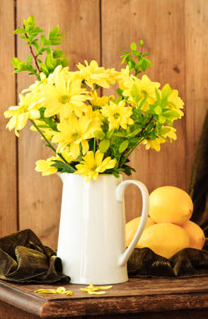 still life: Still life spring flowers and lemons in rustic setting Stock Photo