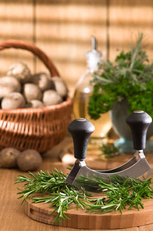 chopping board: Chopping rosemary herbs with mezzaluna knife with new potatoes in basket  Stock Photo