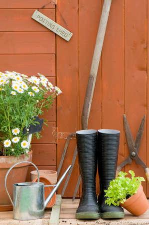 Potting loods met wellington laarzen, tools, gieter en tuin potten  Stockfoto