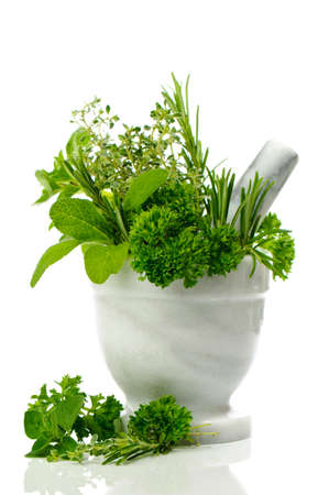 sprigs: Mixed herbs of parsley, sage, rosemary, thyme & oregano in mortar with pestle on white background
