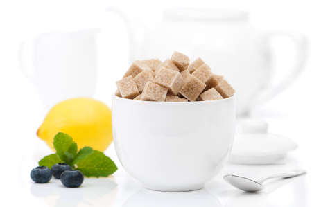 Brown sugar cubes in bowl with teapot and milk jug in background photo