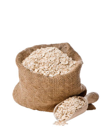 sack: Burlap sack  and scoop of rolled porridge oats isolated on white background Stock Photo