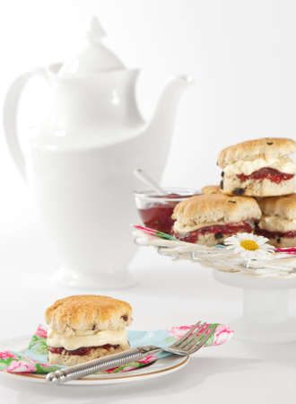Afternoon tea with scones filled with clotted cream and strawberry jam photo