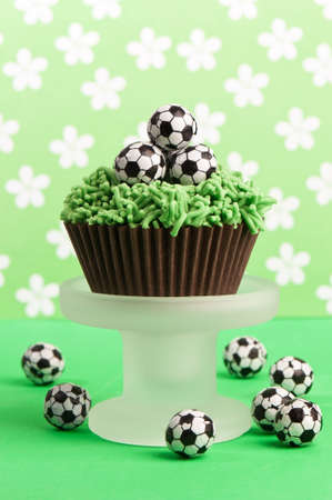 cake ball: Cupcake with grass icing topped with chocolate football decorations Stock Photo