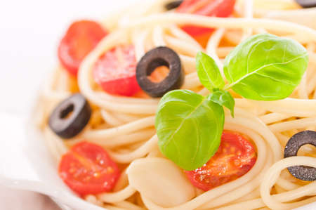 Close up of spaghetti pasta with tomatoes, garlic, and black olives garnished with basil herb Stock Photo - 7257388
