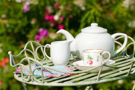 Jardín de partido de té con bonita taza y plato en bandeja de mayordomos  Foto de archivo