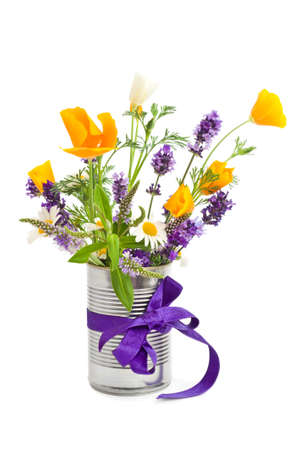 Recycled tin can filled with flowers and tied with purple ribbon on white background