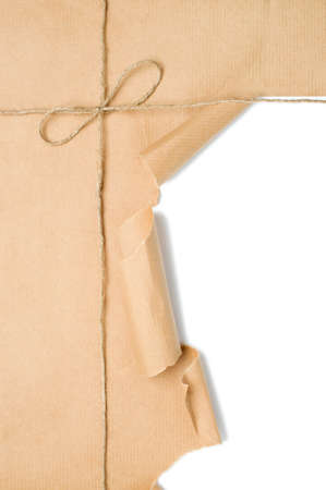 Parcel tied with string with corner open to reveal white copy space photo