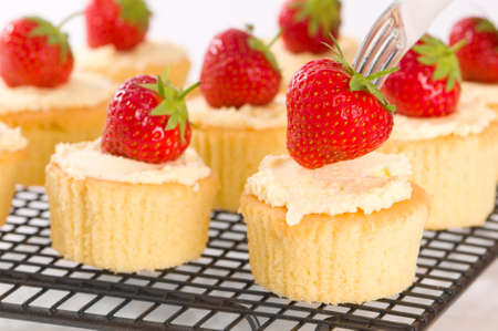 Strawberry on fork topping freshly baked cupcakes photo