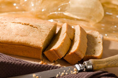 Banana cake loaf cut into slices with knife photo