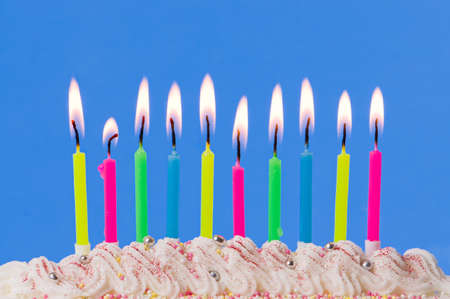Lit birthday candles on decorated cake on blue background