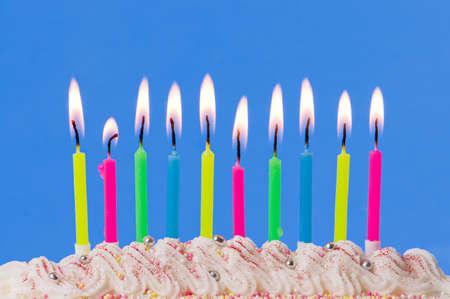 velas de cumplea�os: Velas en su cumplea�os iluminado en pastel decorado sobre fondo azul  Foto de archivo