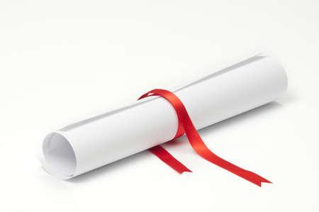 degree: Scorrimento di diploma di laurea legato con nastro rosso su sfondo bianco