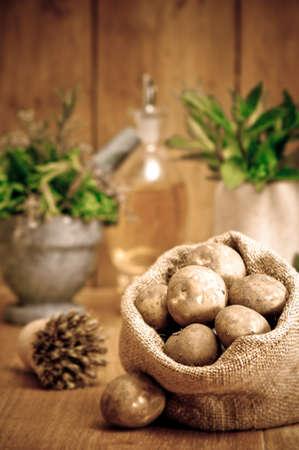 Freshly dug potatoes in burlap sack in rustic setting with herbs in background