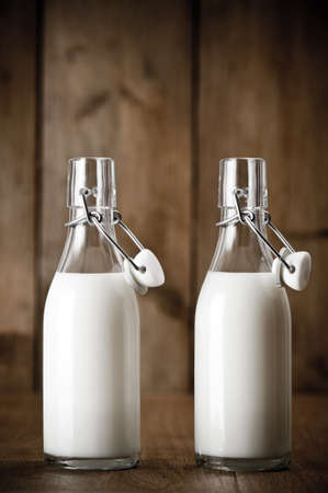 vintage bottle: Fresh milk in old fashioned swing top bottles in rustic setting