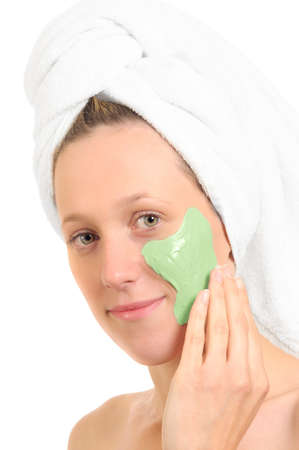 Pretty young woman applying face pack treatment photo