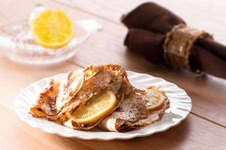 shrove tuesday: Plate of pancakes on a white plate with lemon slices and sprinkled with sugar Stock Photo