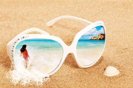 sunglasses: Imagen conceptual de las vacaciones de verano con la escena de la playa en gafas de sol sobre la arena
