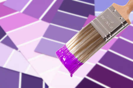 Paint brush loaded with purple paint with colour swatches below photo
