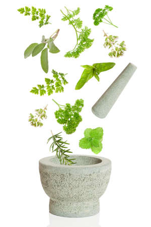 Pestle and herbs falling into mortar on white background