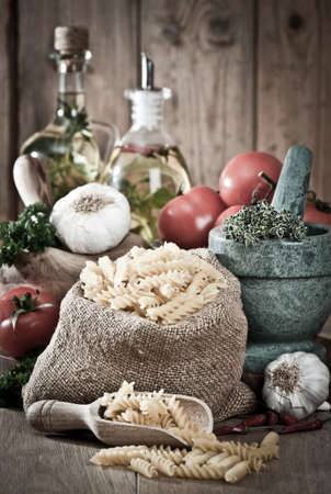 Pasta with garlic and herbs with pestle and mortar in rustic setting